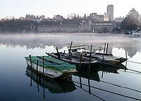 """Trezzo sull'Adda (Milano). Piccole barche ormeggiate sul fiume Adda presso la centrale idroelettrica ENEL """"Taccani"""" (1906) e i resti del Castello Visconteo --- Trezzo sull'Adda (Milan). Small boats moored on Adda river near the ENEL hydroelectric plant """"Taccani"""" (1906) and the ruins of the Visconti castle"""