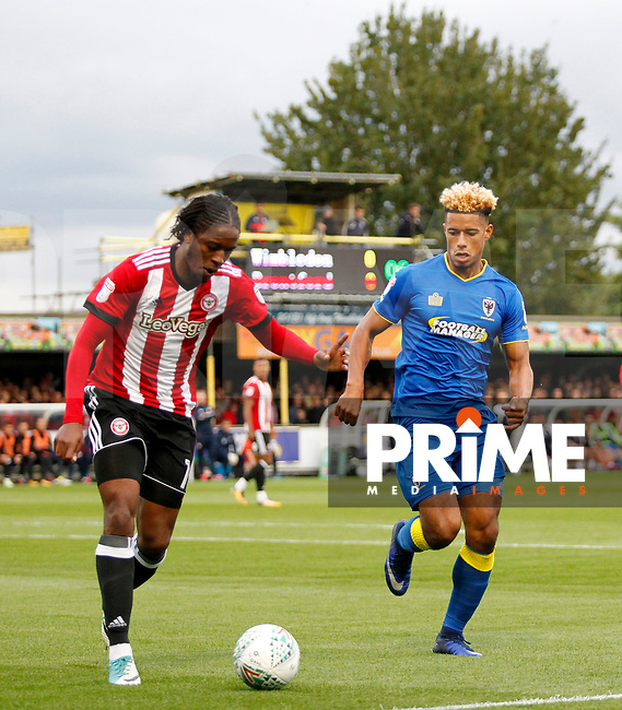 Brentford's Romaine Sawyers is closed down by AFC Wimbledon's Lyle Taylor during the Carabao Cup match between AFC Wimbledon and Brentford at the Cherry Red Records Stadium, Kingston, England on 8 August 2017. Photo by Carlton Myrie.