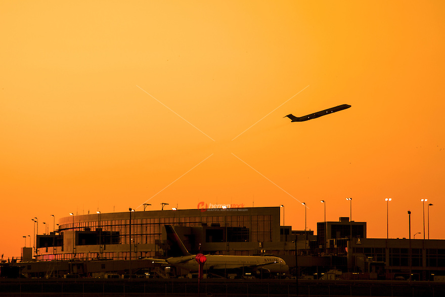 Sunset falls over the Austin–Bergstrom International Airport ABIA Terminal as a jet airline flies overhead, Austin, Texas.