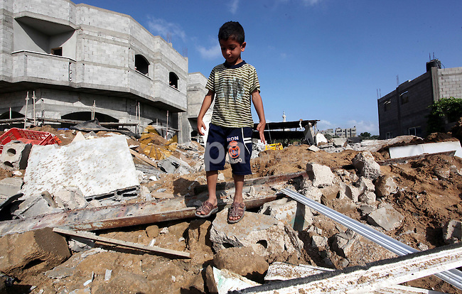 A Palestinian boy inspects the damage at a cheese factory in Gaza City on June 4, 2012 following an Israeli air strike on the Gaza Strip on June 3. Emergency medical sources in Gaza said seven Palestinians were wounded in four strikes, two on targets east of Khan Yunis in the southern part of the territory, and two that hit Beit Lahiya in the northern section of the Strip. Photo by Yasser Fathi