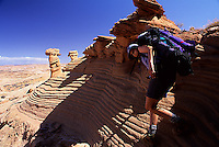 Female hiker deescending a wildly striated sandstone slope, Grand Staircase Escalante National Monument, Utah
