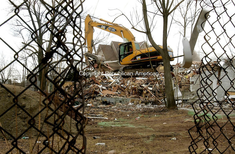 WATERBURY, CT--05 March 2007--030507JS04-Workers from True Blue Environmental Services, LLC, of Wallingford, work on tearing down a blighted property located at 244 Walnut Street in Waterbury. The building was one of three buildings demolished throught the Waterbury Development Corp.'s 'eminent domain' demolition program. The property located at 1032 Bank Street was taken down last week and the propert located at 186 Willow Street will be next.<br /> Jim Shannon / Republican-American