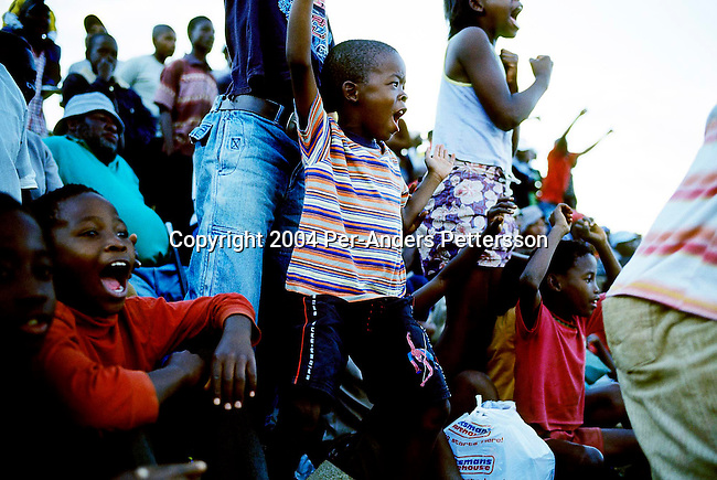 SOWETO, SOUTH AFRICA DECEMBER 27: Spectators cheer during a game at an annual soccer tournament on December 27, 2004 in the Meadowlands section of Soweto, Johannesburg, South Africa. The yearly event draws teams from surrounding townships, and people love the game of soccer in the township. Soweto is South Africa?s largest township and it was founded about one hundred years to make housing available for black people south west of downtown Johannesburg. The estimated population is between 2-3 million. Many key events during the Apartheid struggle unfolded here, and the most known is the student uprisings in June 1976, where thousands of students took to the streets to protest after being forced to study the Afrikaans language at school. Soweto today is a mix of old housing and newly constructed townhouses. A new hungry black middle-class is growing steadily. Most residents work in Johannesburg but the last years many shopping malls has been built, and people are starting to spend their money in Soweto. .(Photo by Per-Anders Pettersson/Getty Images)..