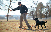 NWA Democrat-Gazette/ANDY SHUPE<br /> Spencer Kass, owner of Kass Kennels and Training, works Thursday, Nov. 15, 2018, with Bella, a golden doodle, on her obedience training at Agri Park in Fayetteville. Kass trains dogs for autistic children and works with aggressive dogs in addition to obedience training.