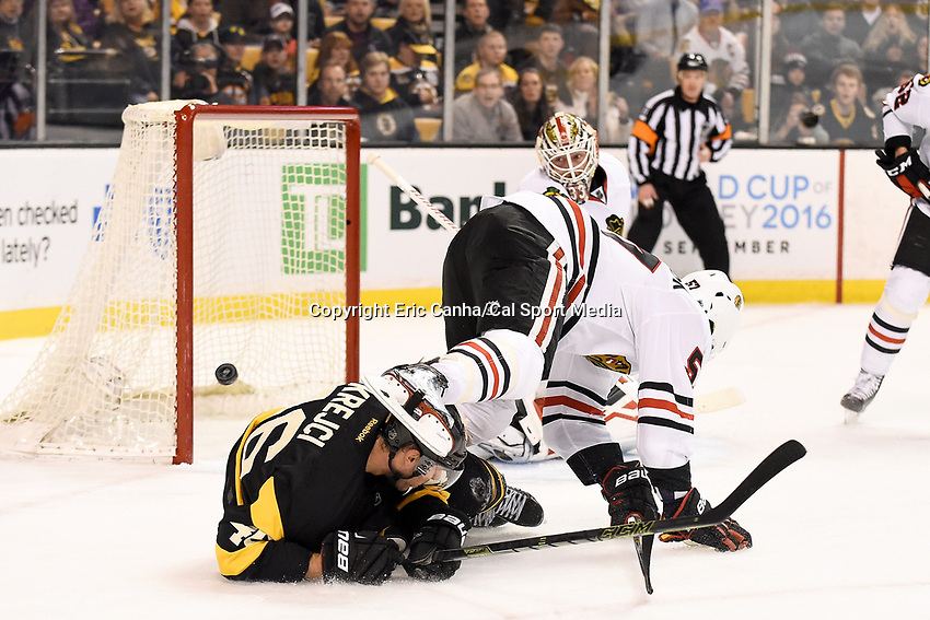 Thursday, March 3, 2016: Chicago Blackhawks defenseman Trevor van Riemsdyk (57) trips over Boston Bruins center David Krejci (46) as goalie Scott Darling (33) keeps his eyes on the puck during the National Hockey League game between the Chicago Blackhawks and the Boston Bruins, held at TD Garden, in Boston, Massachusetts. Eric Canha/CSM