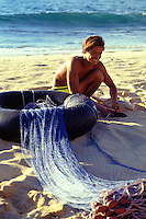 Young man with a fishing net at the north shore of Oahu