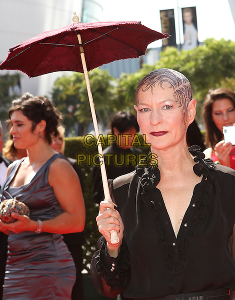 Lou Eyrich.2011 Primetime Creative Arts Emmy AwardsHeld at The Nokia Theatre L.A. Live, Los Angeles, California, USA..September 10th, 2011.half length black blouse sheer umbrella  tattoos shaved head bald.CAP/ADM/KB.©Kevan Brooks/AdMedia/Capital Pictures.