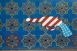 Anti-American mural depicting the Stars and Stripes as a hand gun, outside the former American Embassy, Tehran, Iran, 11 July 2005.<br />