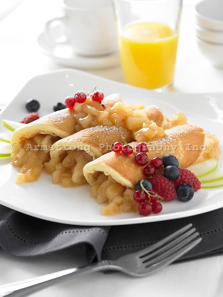 A plate of apple pancakes topped with red currents, blueberries, raspberries, powdered sugar, and green apple slices. Glass of orange juice in background