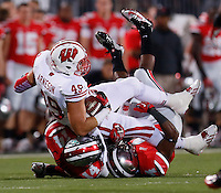 Wisconsin Badgers tight end Sam Arneson (49) is tackled by Ohio State Buckeyes linebacker Curtis Grant (14) and Ohio State Buckeyes safety C.J. Barnett (4) during Saturday's NCAA Division I football game at Ohio Stadium in Columbus on September 28, 2013. (Barbara J. Perenic/Columbus Dispatch)