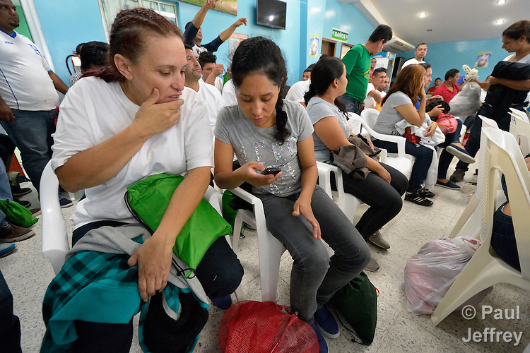 Honduran women deported from the United States use their phones to contact family and friends after they arrived at a church-run center in the San Pedro Sula airport. They were flown to the airport aboard a U.S. government flight, then bused to a remote section of the airport where the Catholic Church operates a Center for Attention to Returned Migrants. The deported are welcomed home and given their phones, shoelaces, belts and other personal belonging that were taken from them before boarding the flight. They are then cleared by immigration officials and offered assistance with seeking jobs or transportation to other places in Honduras.