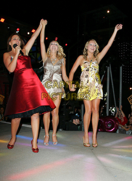 DAVINA McCALL, AMANDA & SAM MARCHANT .At the Grand Final of Big Brother 8.Elstree Studios, Borehamwood, Hertfordshire, England,.31st August 2007 .Herts full length twins runners up gold yellow and white print mini dress dresses red shoes hands arms waving.Ref: CAP/ROS.©Steve Ross/Capital Pictures