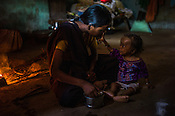 18 month old son, Prahlad RAMESH plays with his mother, Rekha RAMESH as he eats his breakfast in the kitchen of their house in Dhawati VIllage of Khaknar block of Burhanpur district in Madhya Pradesh, India.  Photo: Sanjit Das/Panos for ACF