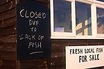 A3ABHC Blackboard sign on small coastal fish shed saying 'closed due to lack of fish'