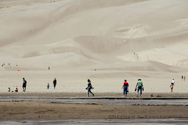 People walk though the Medano Creek in Great Sand Dunes National Park in Colorado.