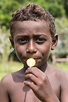 Peava Village, Gatokae Island, Solomon Islands; a young boy eating a lollipop provided by one of the visiting tourists