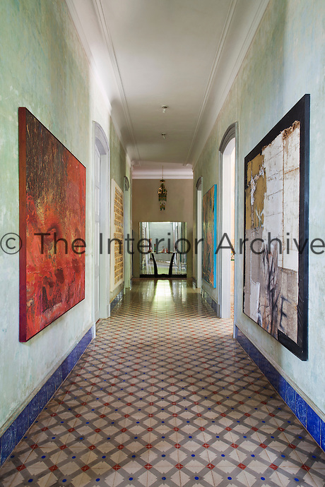 A corridor on the ground floor of the villa is laid with old ceramic tiles and the walls serve as a gallery for a collection of contemporary art