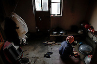 ATTN MICHAEL CARONNA*** TO BE RELEASED WITH TEXT AND TV***..A North Korean woman prepares meal in her house in area damaged by recent floods and typhoons in the Soksa-Ri collective farm in the South Hwanghae province September 29, 2011. Isolated North Korea has appealed for food aid following a series of natural shocks it says have starved the country's public food distribution system of supplies. In South Hwanghae province, which traditionally produces about a third of the country's total cereal supply, officials say a savage, long winter wiped out 65 percent of the barley, wheat and potato crops. Then summer floods and storms destroyed 80 percent of the maize harvest, according to the province's governing People's Committee, and may have an impact on the October rice harvest. Pictures were taken on a government controlled tour for Reuters Alertnet.   REUTERS/Damir Sagolj   (NORTH KOREA)
