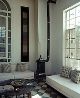 In the living room contemporary banquette-style sofas flank a traditional wood-burning stove