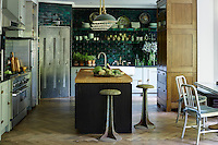The country-style kitchen incorporates dark green, glazed metro tiles to create a signature wall and splash back