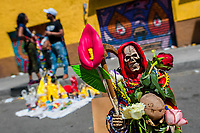 A statue of Santa Muerte (Holy Death), holding fresh flowers, is seen placed on the street during a religious pilgrimage in Tepito, Mexico City, Mexico, 1 April 2018. The religious cult of Santa Muerte is a fusion of Aztec death worship rituals and Catholic beliefs. Born in lower-class neighborhoods of Mexico City, it has always been closely associated with crime. In the past decades, original Santa Muerte followers, such as prostitutes, pickpockets and street drug traffickers, have merged with thousands of ordinary Mexican Catholics. The Holy Death veneration, offering a spiritual way out of hardship in modern society, rapidly expanded. Although the Catholic Church still considers Santa Muerte followers the devil worshippers, on the first day of every month, crowds of Santa Muerte believers fill the streets of Tepito. Holding statues of Holy Death clothed in a long robe, they pray for healing, protection, money or any other favor in life.