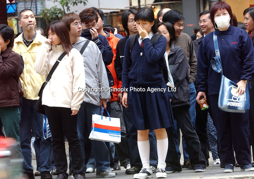 Peopele cover their faces while waiting at an intersection in Causeway Bay, Hong Kong.   The area is one of the most densley populated and polluted..21-SEP-02