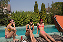 Romania - Timisoara - Domina Monserrat (left), Krina (center) and Nathali Rose (right) take a break around the pool at the Live Cams Mansion before starting their day at work.