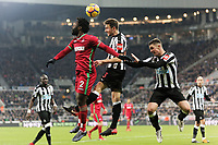 (L-R) Wilfried Bony of Swansea City challenged for a header by Paul Dummett and Ciaran Clark of Newcastle during the Premier League match between Newcastle United and Swansea City at St James' Park, Newcastle, England, UK. Saturday 13 January 2018