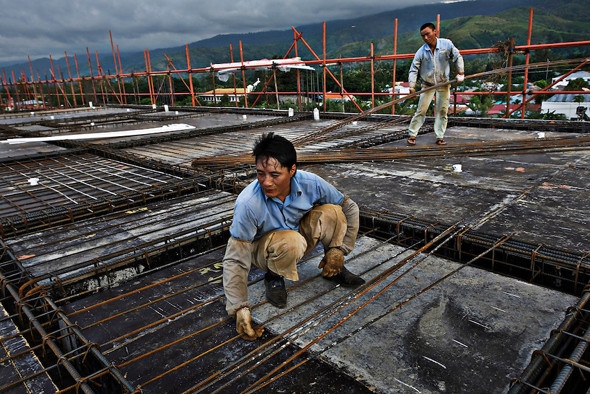 Chinese construction workers lay the framework for a floor of the Timor Plaza, a large shopping center scheduled to be complete in mid-2010, in Dili, East Timor, December 26, 2009.