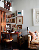 In one corner of the living room is set a small writing area. An eclectic mix of styles of furniture and vintage pieces combine to give the room a retro feel.