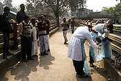 The residents gather to look as the laboratory assistants from the Institute of Serology collect sewage samples from a sewage in Rabindra Nagar in 24 South Pargana, the outskirts of Kolkata to monitor the polio virus in urban Bengal.