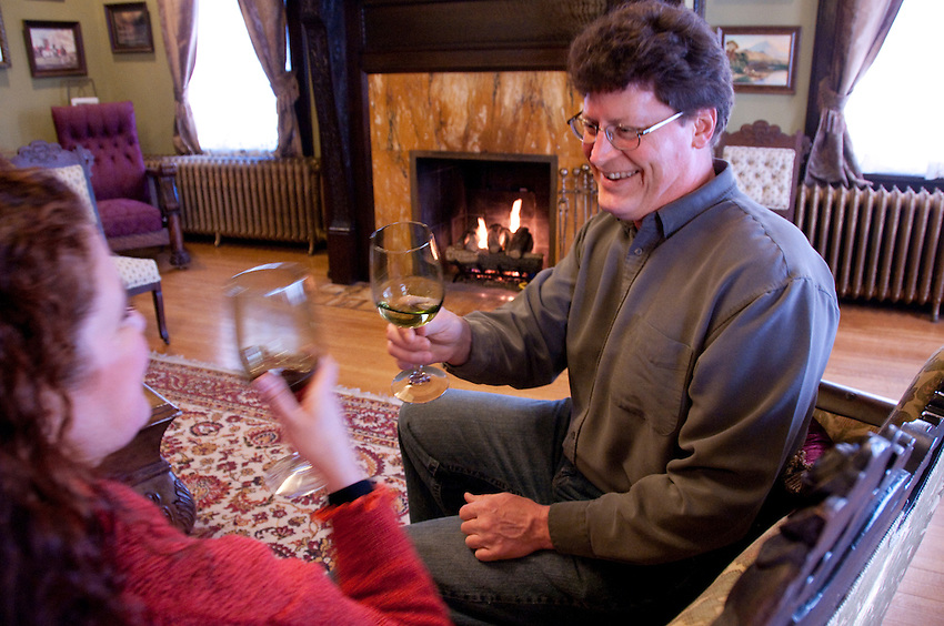 Guests enjoy wine and conversation in front of the fireplace at the Laurium Manor Inn in Laurium Michigan.