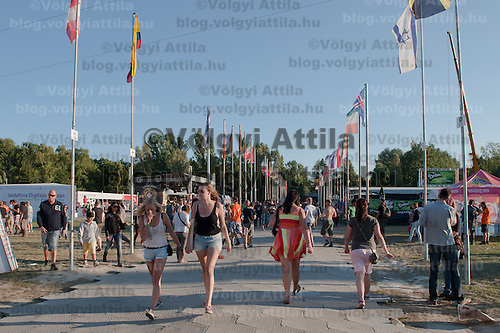 Participants walk on a road between international flags on Sziget festival held in Budapest, Hungary on August 10, 2011. ATTILA VOLGYI