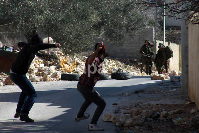 Palestinian protesters throw stones towards Israeli security forces as clashes broke out during a demonstration against the expropriation of Palestinian land by Israel in the village of Kfar Qaddum, near the occupied West Bank city of Nablus, on Dec. 27, 2013. According to reports, ten Palestinians were reportedly wounded during the clashes accompanying the weekly Friday demonstrations of Palestinians against Jewish settlements. The number of wounded Israeli soldiers was not immediately known27, 2013. Photo by Nedal Eshtayah