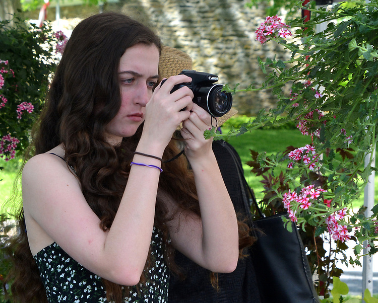 A young visitor seen photographing one of the many flower arrangements displayed on the Opening Day of the 2017 Saugerties Farmer's Market on Saturday, May 27, 2017. Photo by Jim Peppler. Copyright/Jim Peppler-2017.