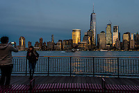 Jersey City, NJ 26 October 2016 =  People taking a snapshot on the Jersey City Waterfront with a view of the Lower Manhattan Skyline with the World Trade Center and World Financial Center in the background.