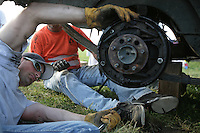 Chris Cantrelle works on the NY LIFE car owned by Shane Van Dalen during the Demolition Derby. Photo by Meryl Schenker..