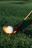 Detail of a golf ball on a tee and a driver.