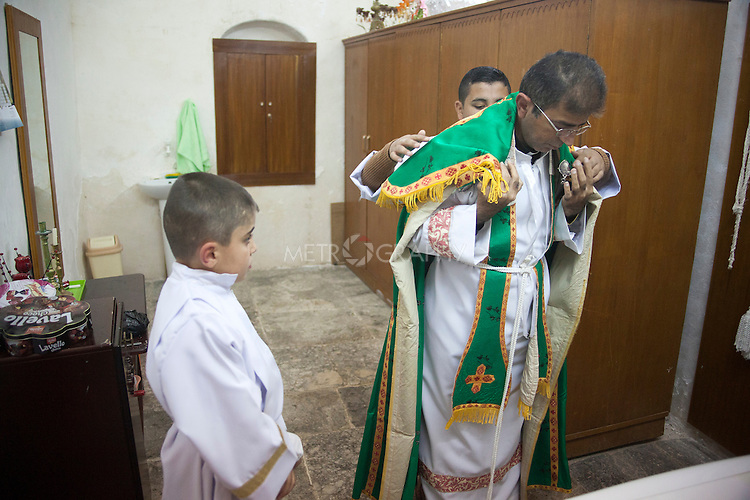 16/11/14. Alqosh, Iraq. Milad (left) and a friend help Father Jobrail, a priest in the church at the Monastery, with his robes.