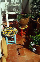 Water runs from a tap into a mosaic tiled bowl on this small sunlit terrace
