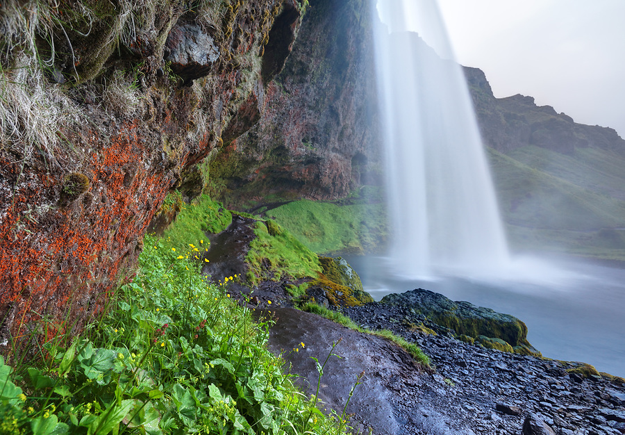 Trail running through cave behind Seljalandsfoss plunge waterfall, South Region, Iceland