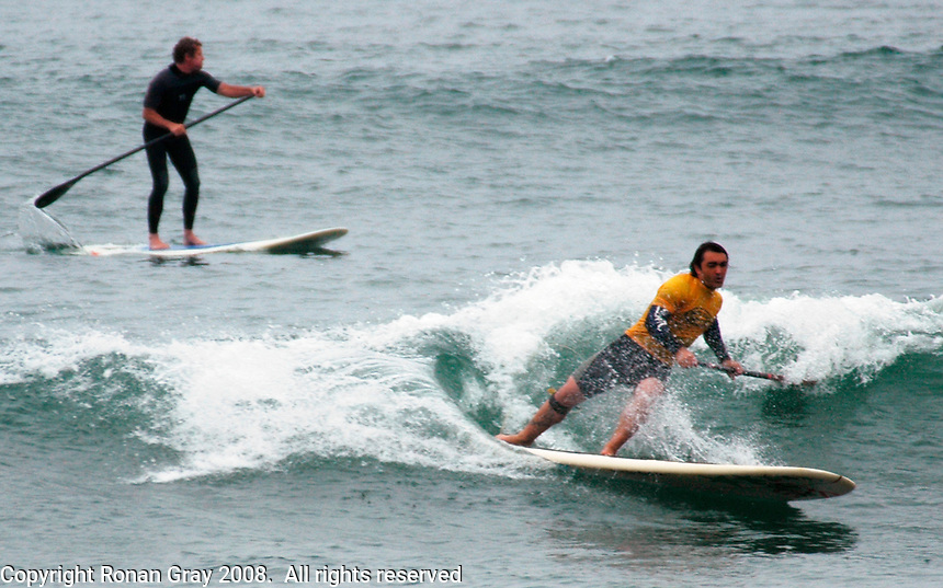 Saturday, June 14, 2008, Tourmaline Surf Park, Pacific Beach, San Diego, CA, USA.  Yann Quilfen (yellow, right)makes a bottom turn as Mike Gillard gets ready to paddle into the next wave during the Semi-Final of the Stand-Up Paddle competition at the Pacific Beach Surf Club's Tenth Annual Longboard Classic at Tourmaline Surfing Park.  Both  advanced to the final and Quilfen won the SUP competition.  It was the first year that SUP has been included in the Long Board Classic.  The event was well attended despite gray, June gloom clouds and fickle, windy surf conditions.