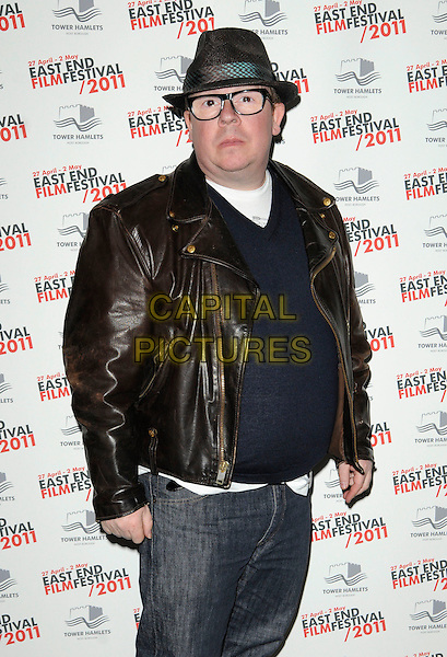 "PERRY BENSON .at ""The Libertines - There Are No Innocent Bystanders"" East End Film Festival opening gala premiere, The Troxy, Shadwell, London, England, UK, .April 27th 2011..half length brown leather jacket hat glasses navy jumper sweater jeans .CAP/CAN.©Can Nguyen/Capital Pictures."