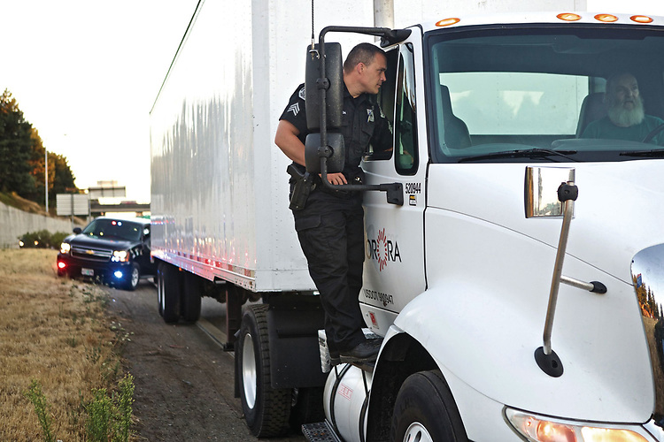 Portland Police Sgt. David Abrahamson, who oversees the bureaus fatal crash team, talks with a truck driver he stopped for speeding on I-5 one recent night. Officers statewide are getting refreshed in training to recognize and evaluate drug-affected motorists since recreational marijuana legalization in Oregon. , Portland Tribune - News