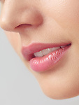Closeup of young woman mouth with pink lipstick on slightly open lips