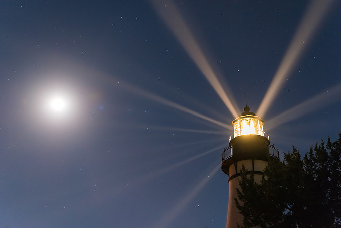 The historic lighthouse on Amelia Island. The rays of light shine in the early evening, with the rising moon in the distance.