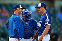 Oklahoma City Dodgers pitching coach Scott Radinsky (36) talks with pitcher Eric Surkamp (41) as catcher Brian Ward (10) listens in during a game against the Fresno Grizzles on June 1, 2015 at Chickasaw Bricktown Ballpark in Oklahoma City, Oklahoma.  Fresno defeated Oklahoma City 14-1.  (Mike Janes/Four Seam Images)