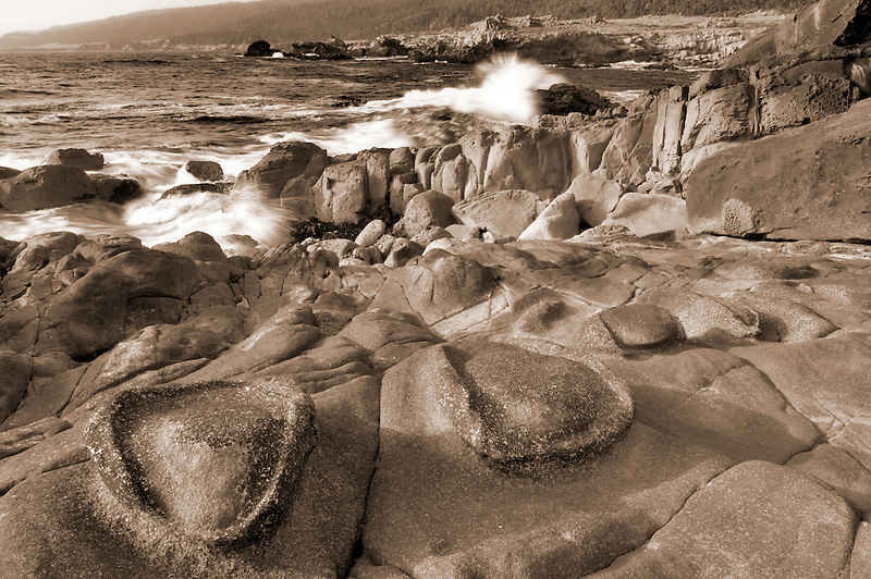 Unusual rock formation in sandstone formation and crashing waves. Salt Point State Park. California
