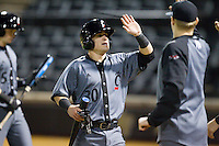 Ryan Quinn (30) of the Cincinnati Bearcats high fives teammates after scoring a run against the Wake Forest Demon Deacons at Wake Forest Baseball Park on February 21, 2014 in Winston-Salem, North Carolina.  The Bearcats defeated the Demon Deacons 5-0.  (Brian Westerholt/Four Seam Images)