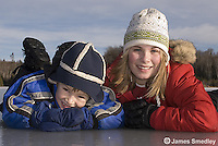 Happy young girl and boy lying on the frozen lake ice